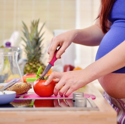 pregnant woman prepares a meal